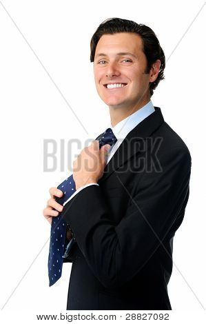 Handsome man adjusts his tie while getting ready to work