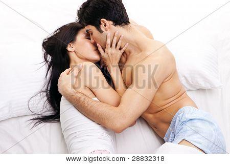 An attractive young couple in a loving embrace kissing one another in bed.