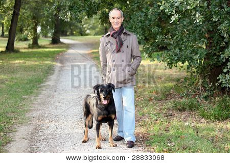 Senior man walking his dog in the woods