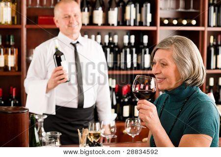 Wine bar senior woman enjoy wine glass in front of bartender