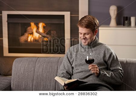 Young man sitting on sofa at home on a cold winter day, reading book in front of fireplace, tasting red wine.?