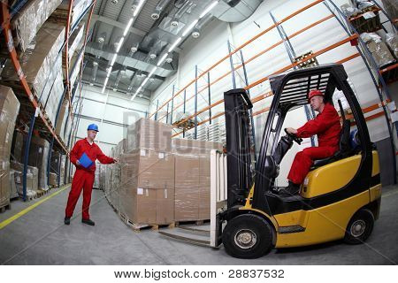 goods delivery in storehouse, two workers  reloading pallets  with  forklift truck