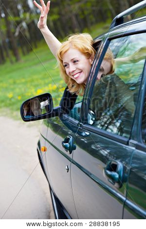 A smiling blond woman in a car is wagging