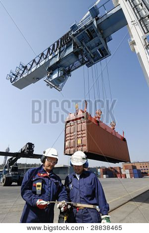 dock workers in container-port, cranes and trucks inside commercial dock.