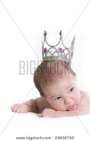 studio portrait of newborn baby in toy crown over white