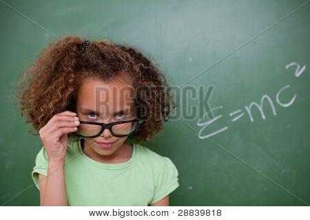 Schoolgirl looking above her glasses in front of a blackboard