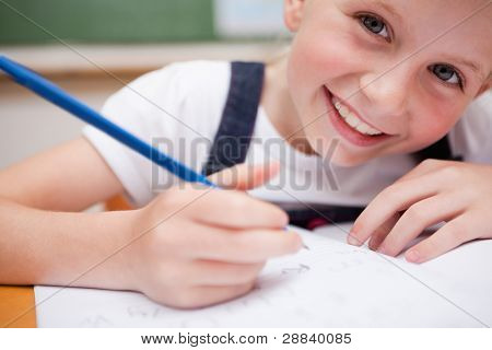 Close up of a smiling schoolgirl writing something in a classroom