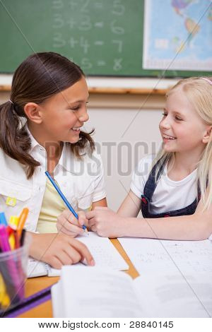 Portrait of happy pupils working together on an assignment in a classroom