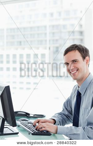 Side view of a happy office worker using a monitor in his office