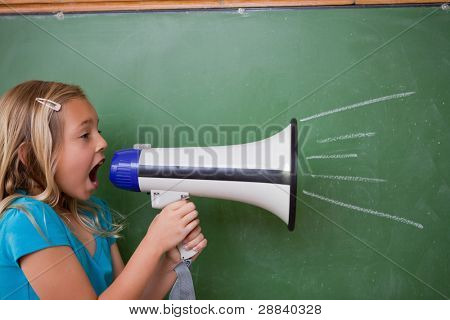 Young schoolgirl screaming through a megaphone in front of blackboard