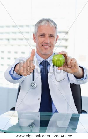 Portrait of a doctor showing an apple with the thumb up in his office