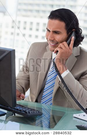 Portrait of a businessman working with a monitor while being on the phone in his office