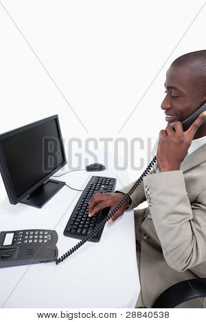 Side view of a male secretary answering the phone while using a computer against a white background