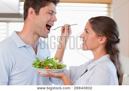 Accomplice couple tasting a salad in their kitchen
