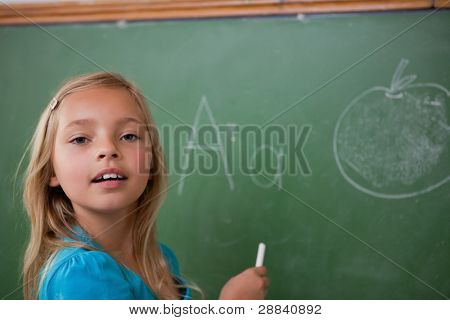 Young schoolgirl learning the alphabet on a blackboard