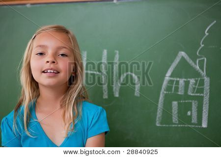 Blonde schoolgirl posing in front of a blackboard in a classroom