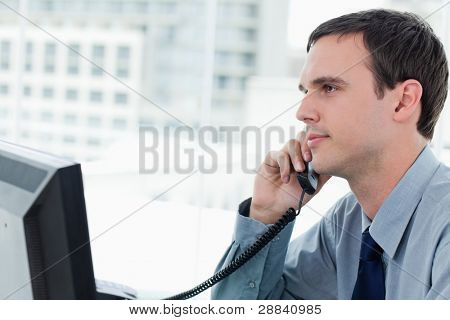 Young office worker on the phone`in his office