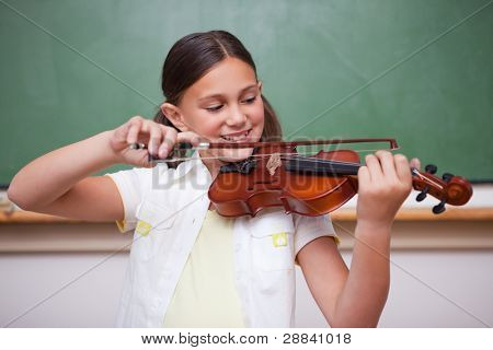 Schoolgirl playing the violin in a classroom