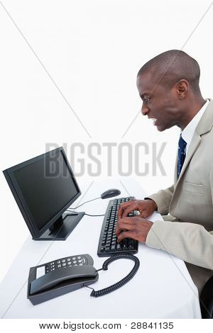 Side view of an angry businessman using a computer against a white background
