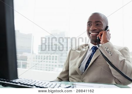 Smiling businessman on the phone in his office