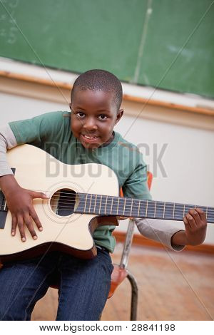 Portrait of a schoolboy playing the guitar in a classroom