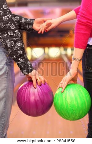Female and male hands with balls in bowling club; man and woman holding hands