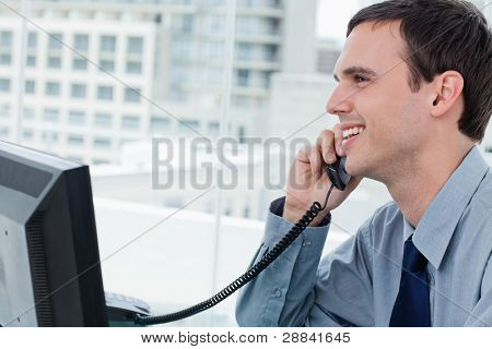 Smiling office worker on the phone in his office