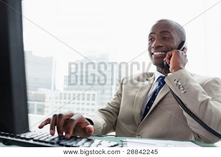 Businessman on the phone while using a computer in his office