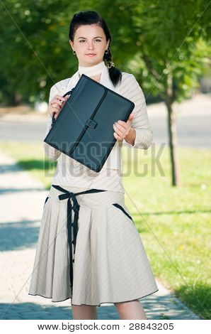 Modern young business woman with briefcase in park outdoors