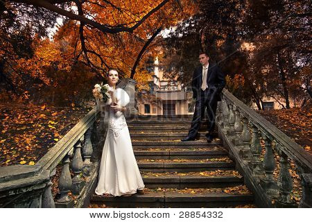 Wedding shot of bride and groom in autumn park