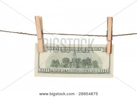 One hundred dollar bills is hanging on a rope with wooden clothespin isolated on white