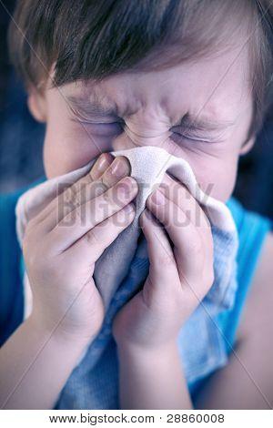 Boy blows his nose into a handkerchief