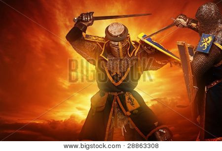 Two medieval knights fights against stormy sky background.