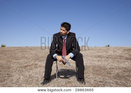 Businessman sit in a chair in outdoor with a handgun