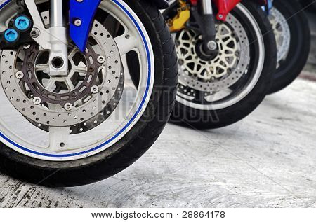 Row of three motorcycle wheels parked in a road