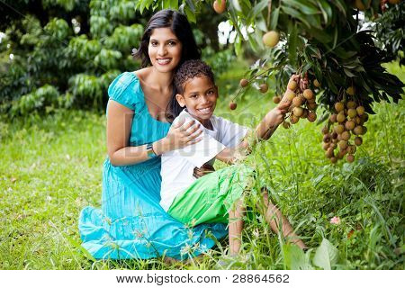 happy young mom and boy picking lychees