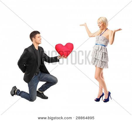 A romantic man on his knees holding a red heart shaped pillow and an excited blond woman isolated on white background