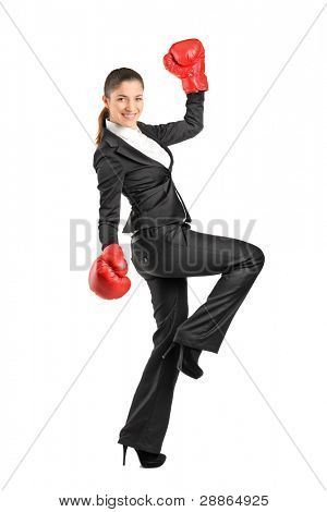 Full length portrait of a beautiful business woman wearing boxing gloves isolated on white background