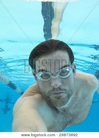 man swimming underwater, shot from below surface