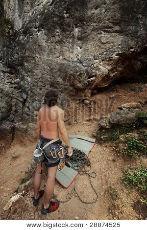 Young man looking to a vertical rocky wall and going to climb