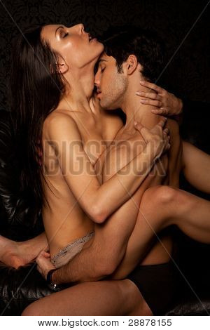 Young naked couple having implied passionate erotic sex, woman in skimpy panties.