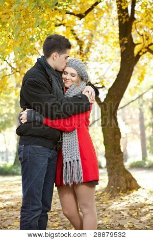 young man kissing his girlfriend, romantic autumn park
