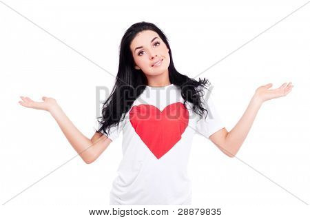beautiful young woman wearing a T-shirt with a big red heart and holding her hands up- place your product here, isolated against white background