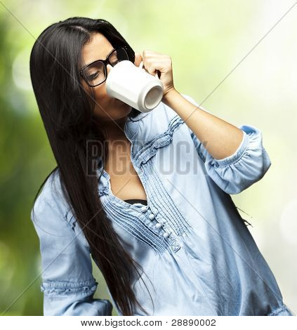 portrait of a pretty young woman drinking coffee on a cup against a nature background