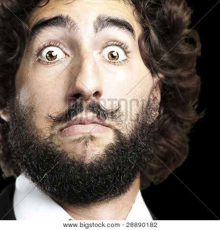 portrait of young man face afraid against a black background