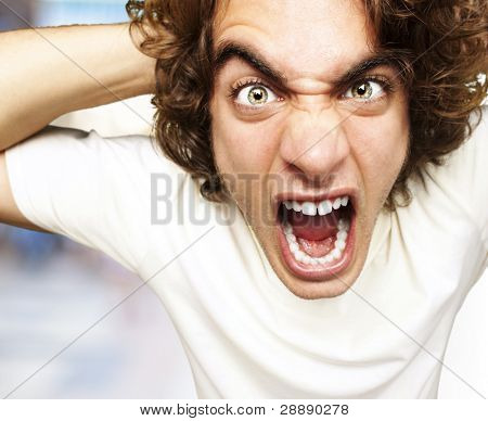 portrait of furious young man shouting against a abstract background