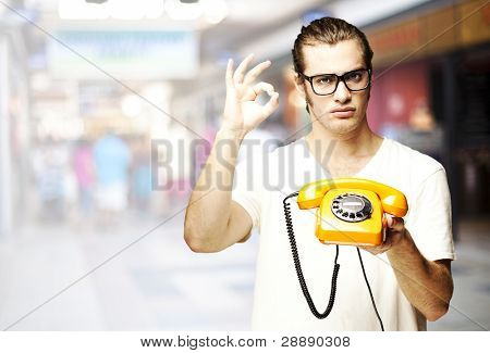portrait of young man holding a vintage telephone and gesturing at crowded place