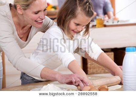 A mother teaching her daughter how to bake.