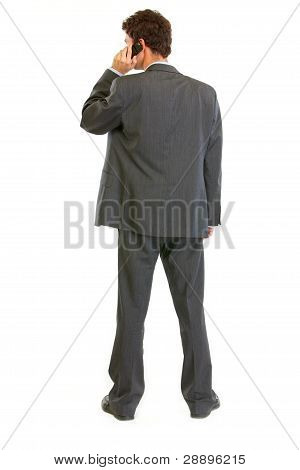 Modern Businessman Standing Back To Camera And Talking Mobile