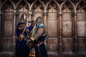 Two knights fighting aganist medieval cathedral wall.